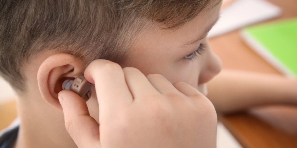 picture of a child putting in his hearing aids from platinum hearing aids in detroit